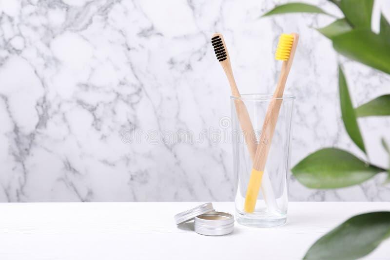 Szkło z bambusowymi toothbrushes i pastą na stole przeciw marmurowemu tłu zdjęcia stock