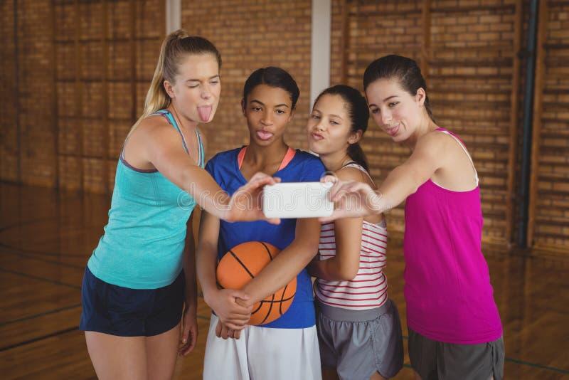 Szkół średnich dziewczyny robi śmiesznym twarzom podczas gdy brać selfie w boisko do koszykówki zdjęcia stock