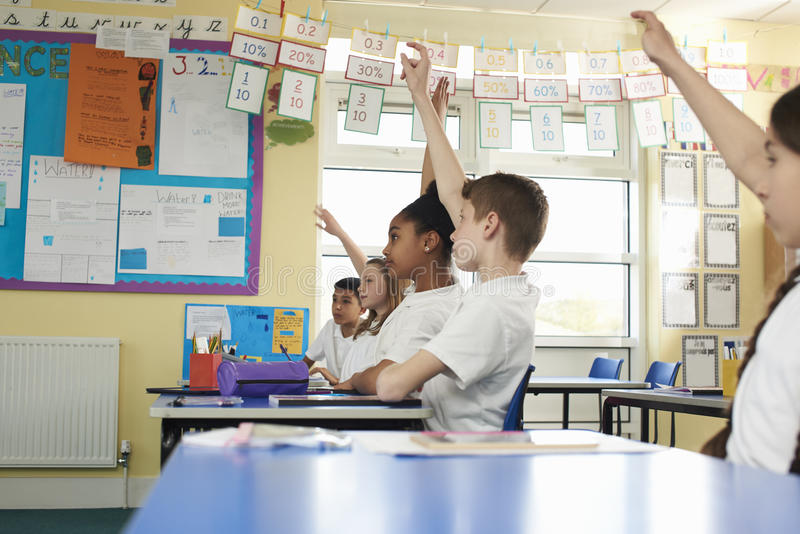 Szkół podstawowych dzieci podnosi ręki w klasie, niski kąt obraz royalty free