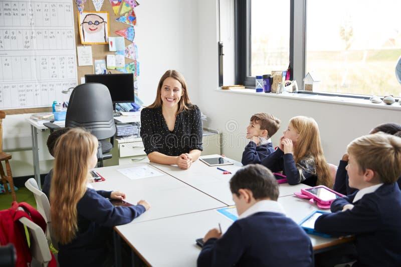 Szkół podstawowych dzieci siedzi przy stołem w sali lekcyjnej z ich żeńskim nauczycielem, patrzeje each inny fotografia stock