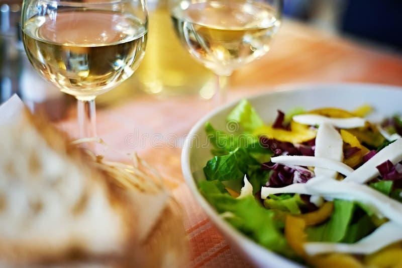 Szkła biały wino i sałatka na stołowej kawiarni obrazy stock