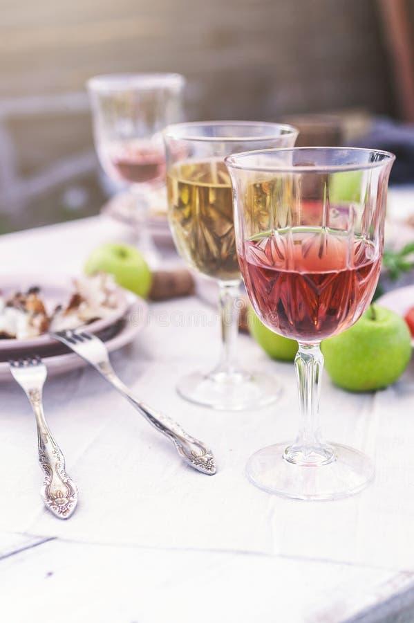 Szkła biel, różany wino, piec na grillu rybi talerze, warzywa, sałatka i owoc na stole, Lata przyjęcie w podwórko obraz royalty free