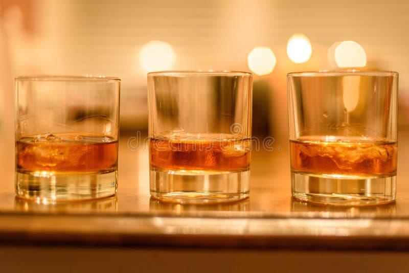 Szkła bourbonu whisky wykładali up na stole z blaskiem świecy wewnątrz fotografia royalty free