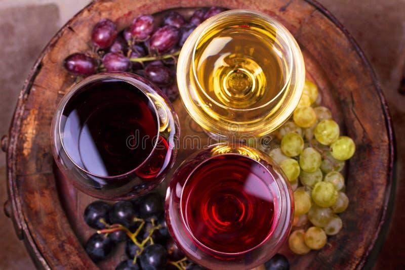 Szkła czerwieni, różanego i białego wino z winogronem w wino lochu, Jedzenie i napoju pojęcie zdjęcie stock