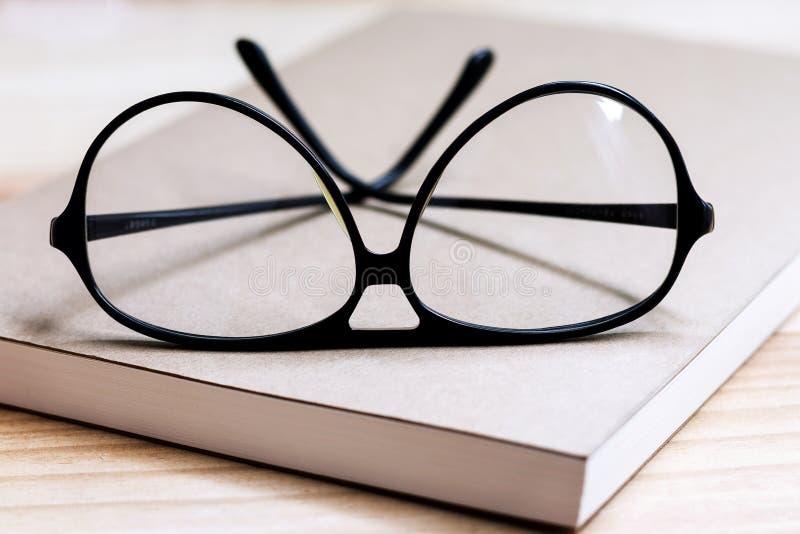 Szkła i książka na drewnianym stole zdjęcia stock