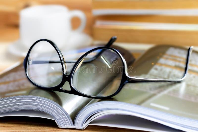 Szkła i książka na drewnianym stole obrazy stock
