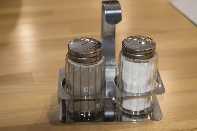 Szkła i metalu solankowy ustalony potrząsacz na drewnianym stole w kawiarni, w górę obrazy stock