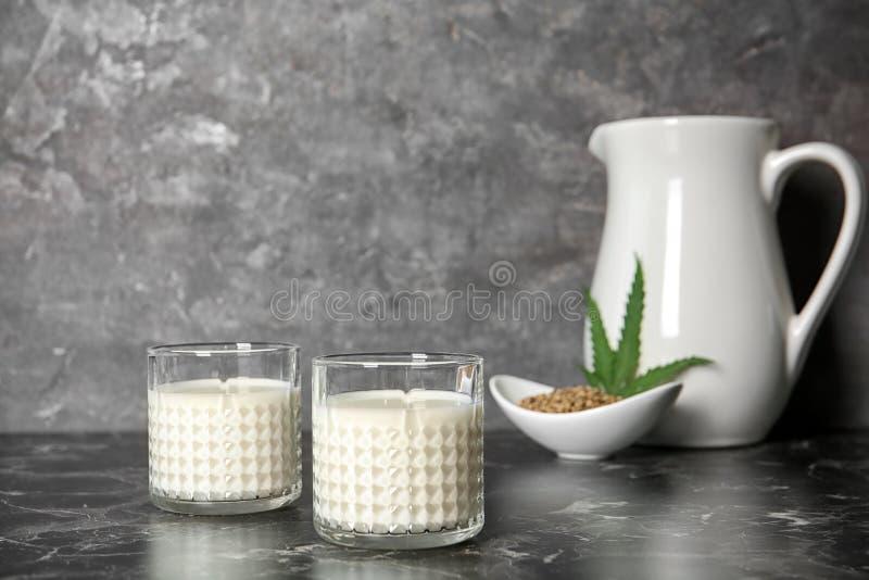 Szkła konopie mleko na stole zdjęcie stock