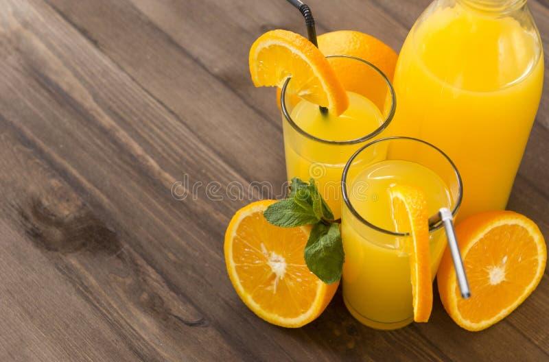 2 szkła sok pomarańczowy z plasterkami pomarańcze i sprigs mennica, butelka sok pomarańczowy, połówka pomarańcze na brązi obraz royalty free
