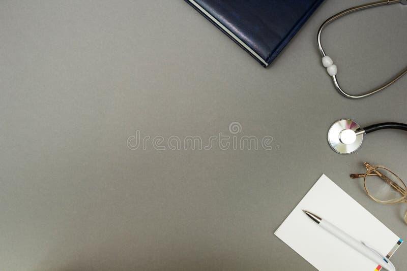 Szkła, stetoskop i notatnik na szarym tle, pojęcie obrazy royalty free