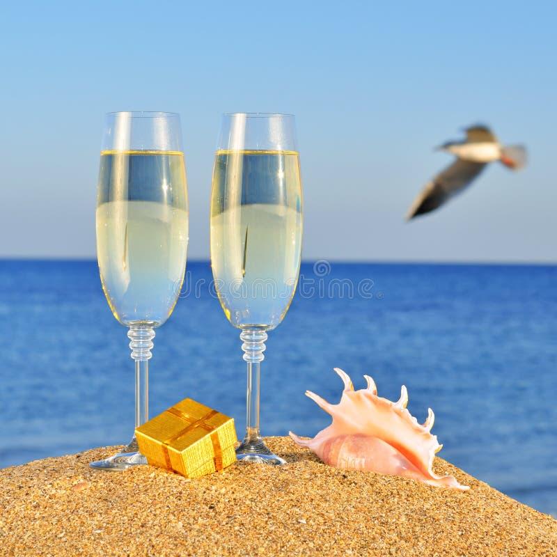 Szkła szampan, pudełko z prezentem i seashel, obrazy royalty free