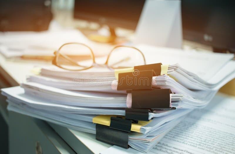 Szkła umieszczający na Niedokończonych dokument stertach papierowi segregatory na komputerowym biurku dla raportu, stosy niedo fotografia royalty free