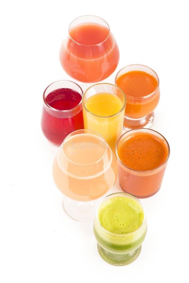 Szkła z świeżymi organicznie jarzynowymi i owocowymi sokami odizolowywającymi na bielu obraz stock
