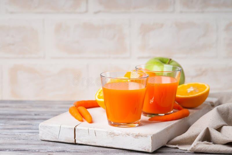 Szkła z marchwianym sokiem, jabłkiem i pokrojoną pomarańcze, fotografia royalty free