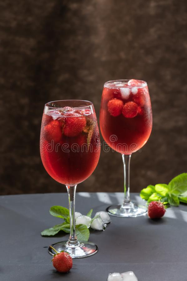 Szkła z odświeżającym napojem z truskawkami i mennicą na stole obraz stock