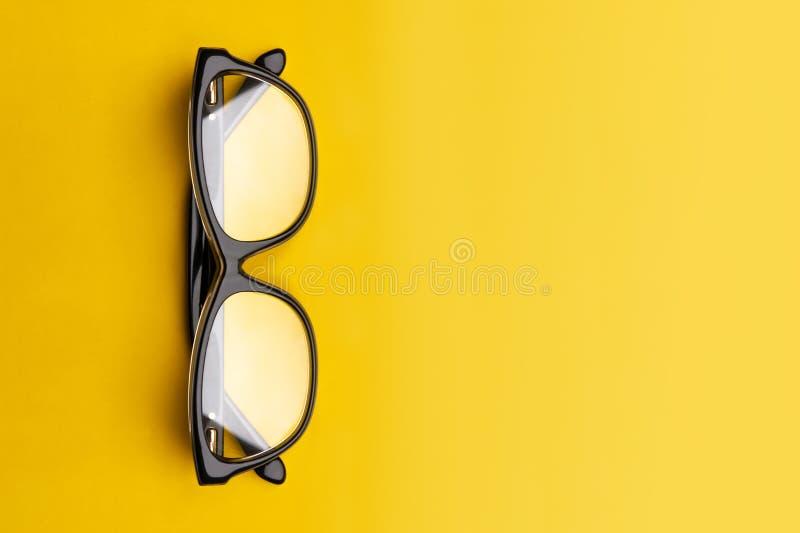 Szkła z przejrzystymi obiektywami odizolowywającymi na żółtym tle Frontowy widok z kopii przestrzeni? obraz stock