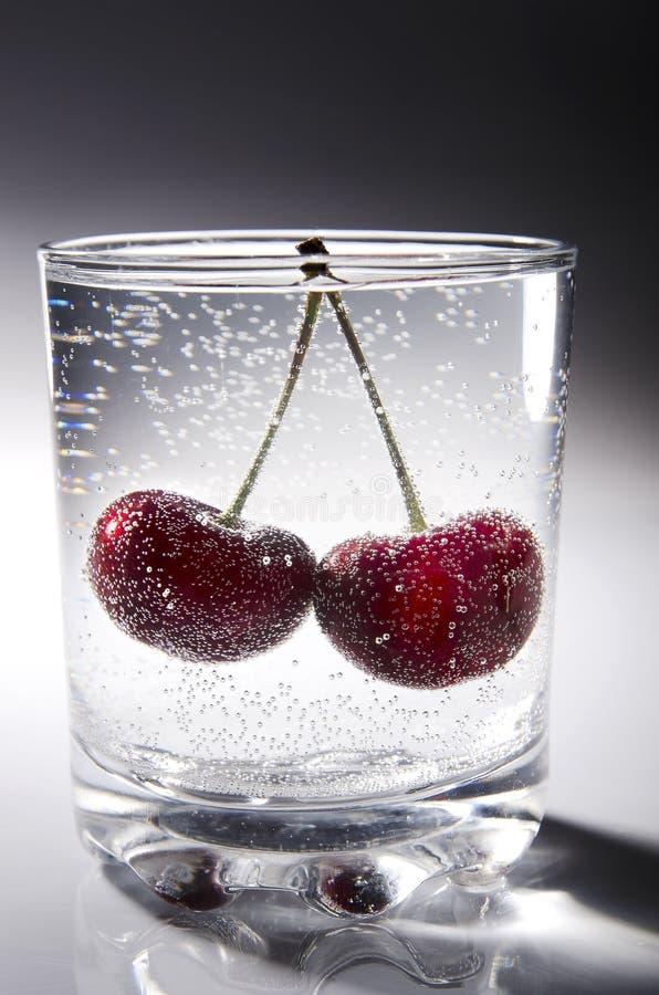 Szkło świeża, zazębiona woda mineralna od halnej wiosny z dwa soczystym, dojrzałe, czerwone czereśniowe jagody na szarym świecący zdjęcie stock