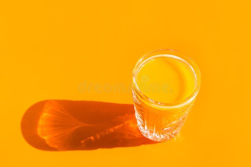 Szkło świeżo gniosący sok pomarańczowy z brają na tony tle Srodzy lekcy ci??cy cienie Wystrza? sztuki 80s stylu estetyka obrazy royalty free