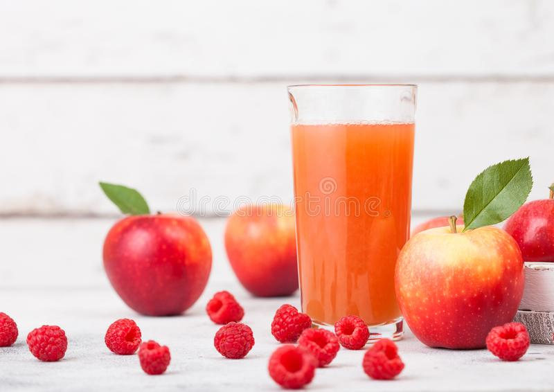 Szkło świeży organicznie jabłka i malinki sok z świeżymi owoc w pudełku na drewnianym tle obrazy stock