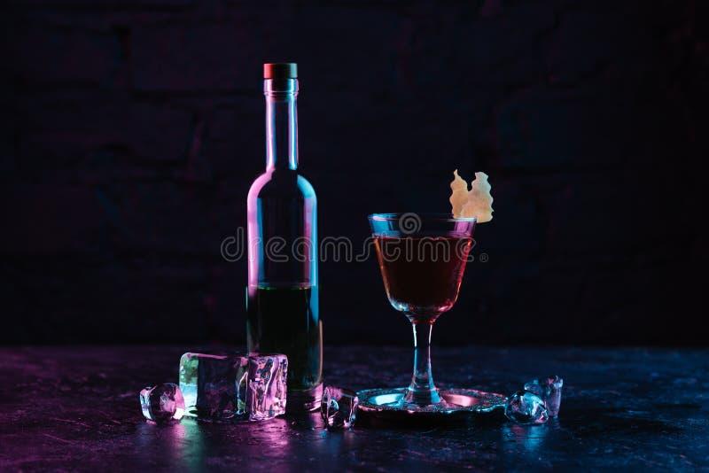 szkło alkoholu koktajl, butelka trunek i kostki lodu na zmroku, ukazujemy się obraz stock