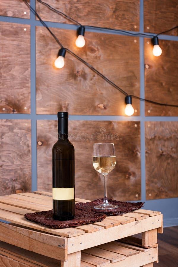 Szkło biały wino i butelka w nowożytnym loft wnętrzu z lekką girlandą na drewnianej ścianie obrazy stock