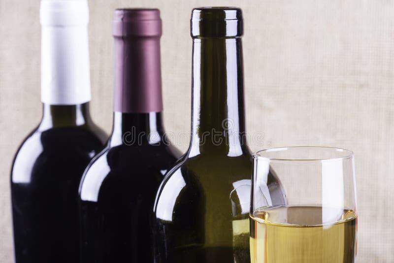 Szkło biały wino na tło butelkach zdjęcie stock