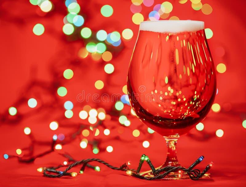 Szkło bladego lager ale z bożonarodzeniowymi światłami na czerwonym tle lub piwo zdjęcie stock