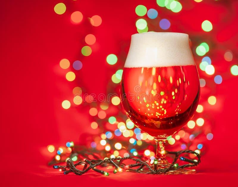 Szkło bladego lager ale z bożonarodzeniowymi światłami na czerwonym tle lub piwo obraz royalty free