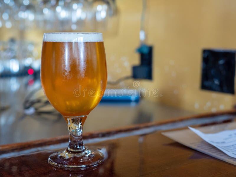 Szkło blady piwny obsiadanie na odpierającym wierzchołku przy barem z pianą zdjęcie stock