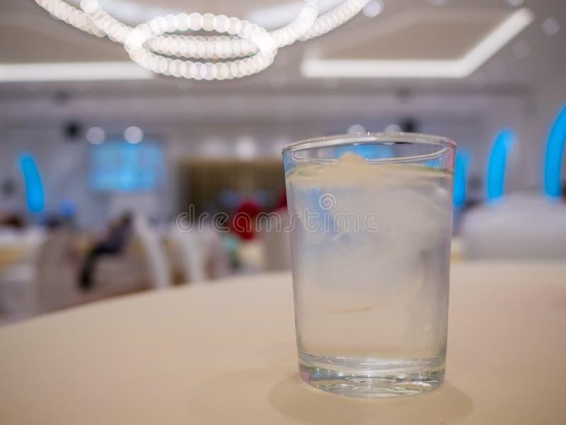 Szkło Chłodno świeży napój z kostką lodu na stole w ślubnej ceremonii świętowania bokeh tle kolorowym i ludzie zamazujemy obrazy stock
