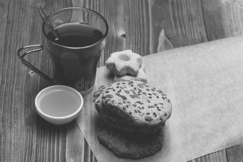 Szkło czarna herbata z oatmeal i gwiazdą kształtował ciastka na białym płótnie Gorący napoju i ciasta pojęcie Skład obraz royalty free