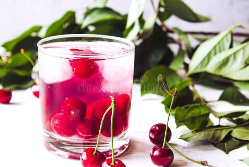 Szkło czereśniowy napój z lodem w szkle na białym drewnianym tle Świeży lato koktajl z wiśniami i kostka lodu obraz stock