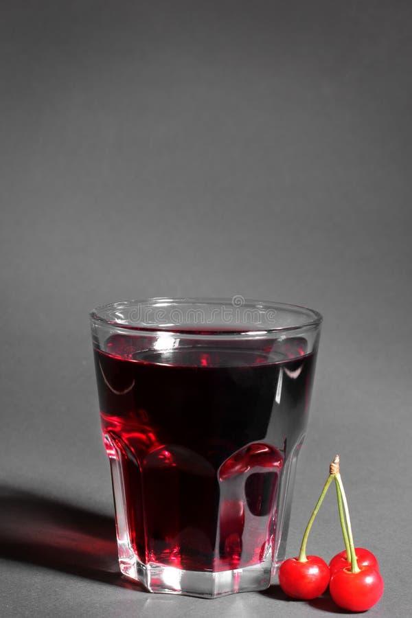 Szkło czereśniowy sok obok wiązki dojrzały, wiśnie na czarnym tle zdjęcie royalty free