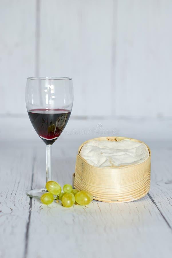 Szkło czerwone wino, biali winogrona i camembert ser w drewnianym pudełku, - vertical zdjęcia stock