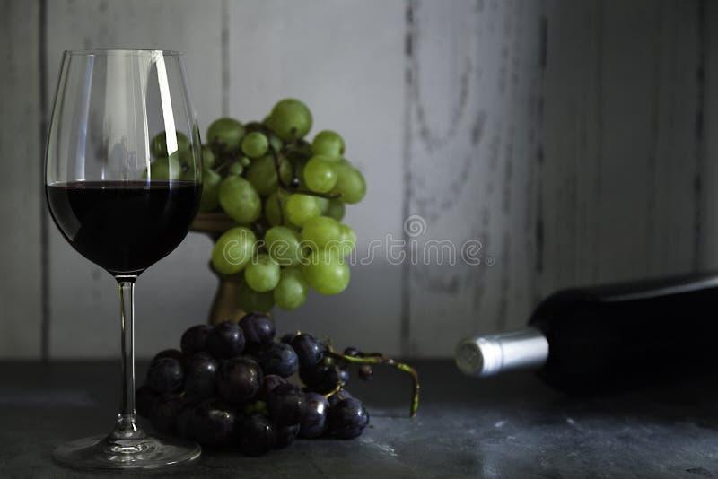 Szkło czerwone wino i wiązka winogrona czerwoni i biali zdjęcia royalty free