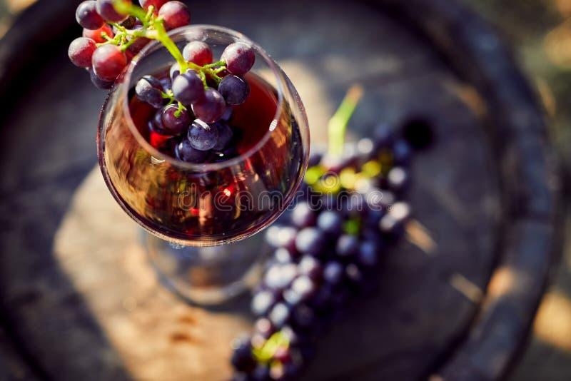 Szkło czerwone wino na drewnianej baryłce z winogronami zdjęcia royalty free