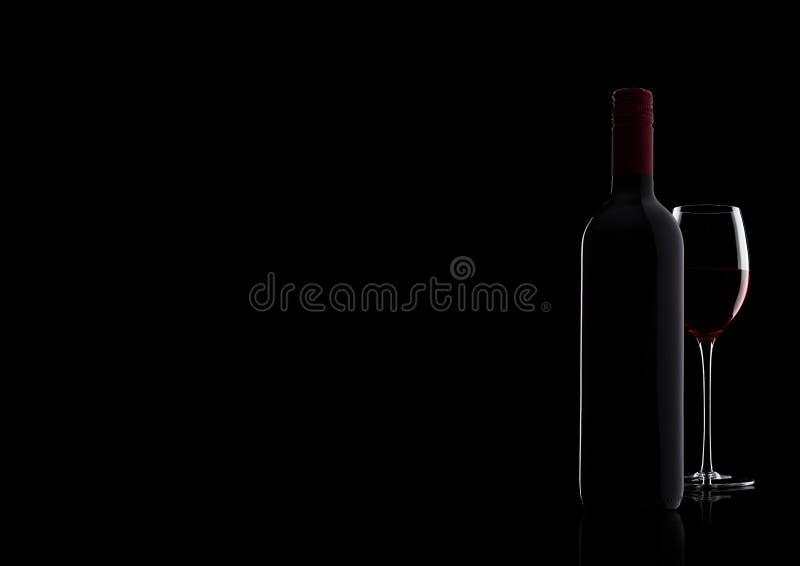Szkło czerwone wino z butelką z kształtem na czerni obraz stock