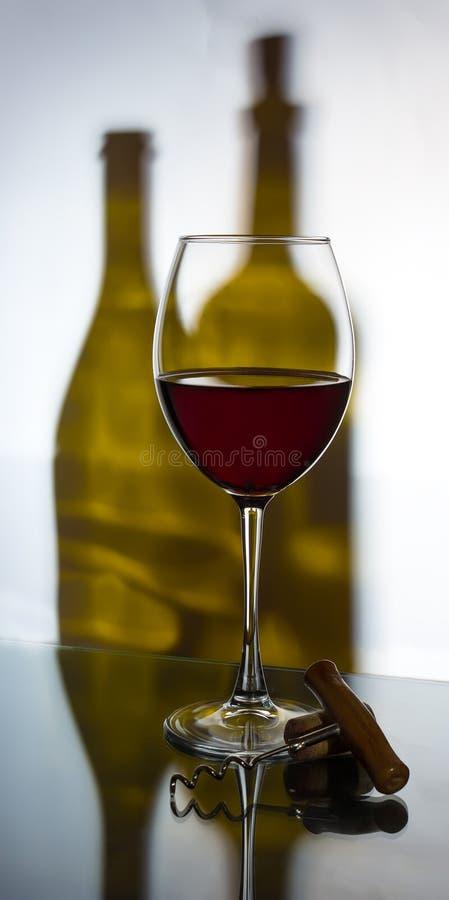 Szkło czerwone wino z corkscrew na tle dwa wi zdjęcia royalty free