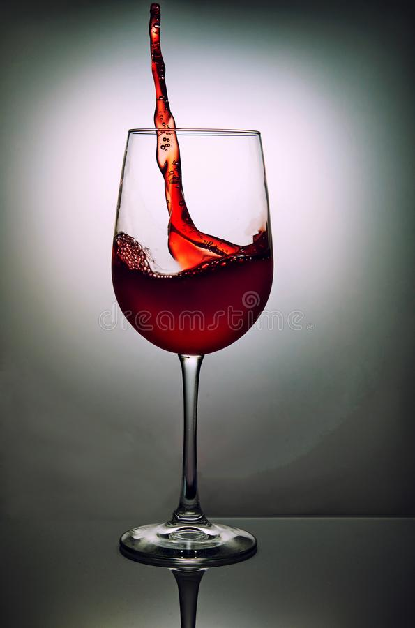 Szkło czerwone wino z falą na popielatym tle obraz royalty free