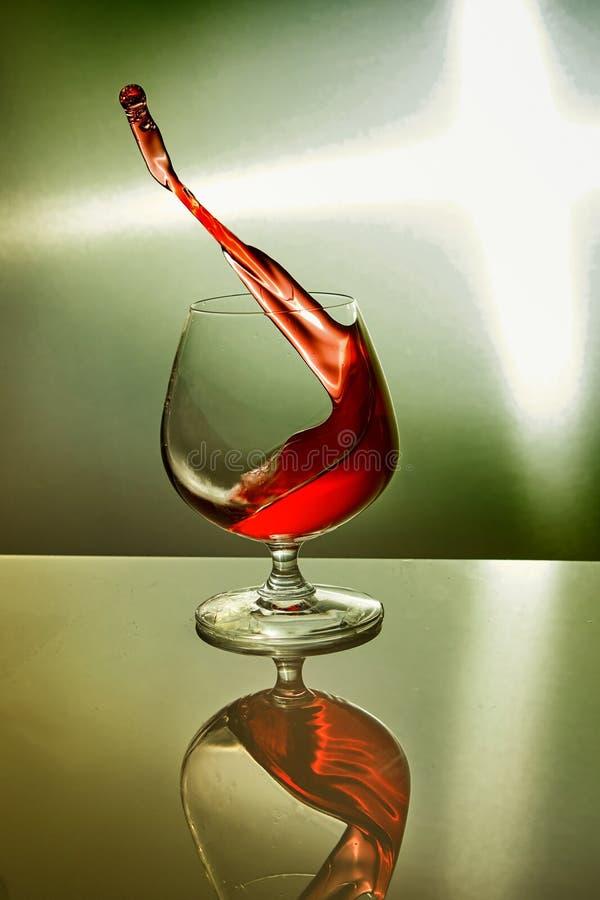 Szkło czerwone wino z falą na zielonym tle fotografia royalty free