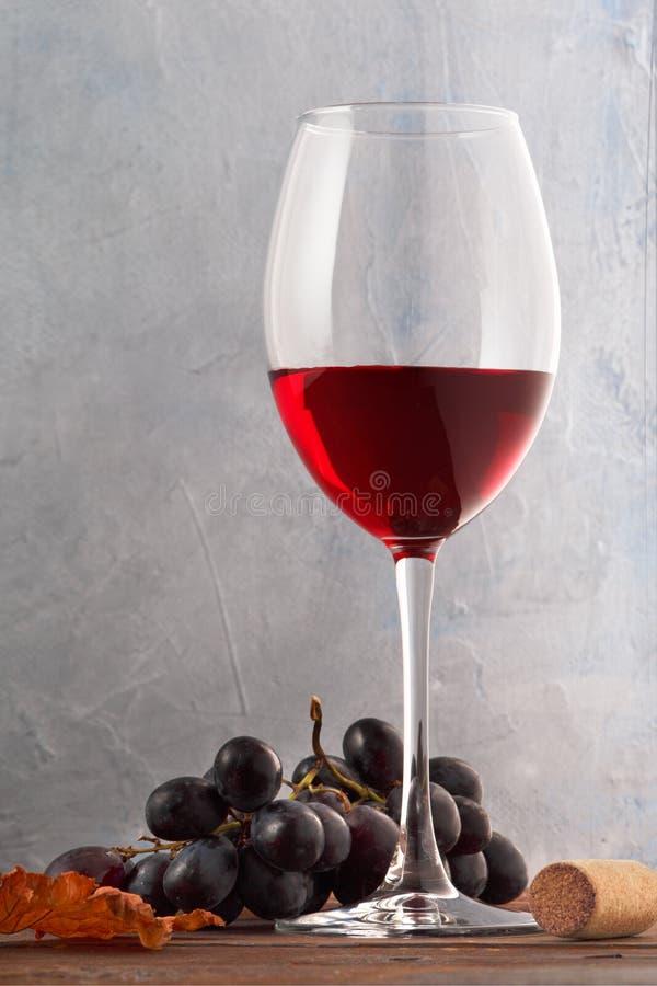 Szk?o czerwone wino z winogronami i korek na drewnianym stole zdjęcie stock