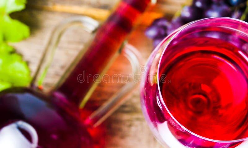 Szkło czerwone wino z winogronem na nieociosanym drewnianym tle zdjęcia stock