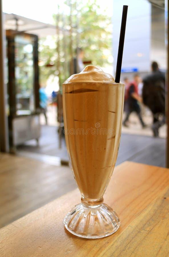 Szkło Frappe kawa na stole z Ruchliwie miasto sceną w tle obraz stock