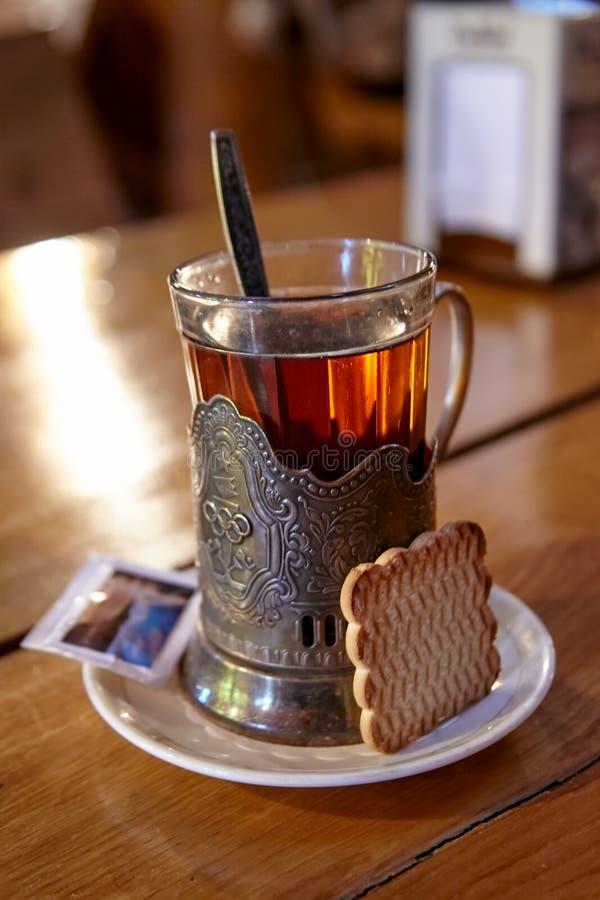 Szk?o herbata w starym rocznika metalu w?a?cicielu z ciastkiem i cukierem na drewnianym stole zdjęcia stock