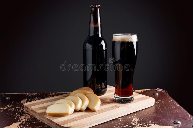Szkło i butelka ciemny piwo z uwędzonym serem na tnącym knurze fotografia stock