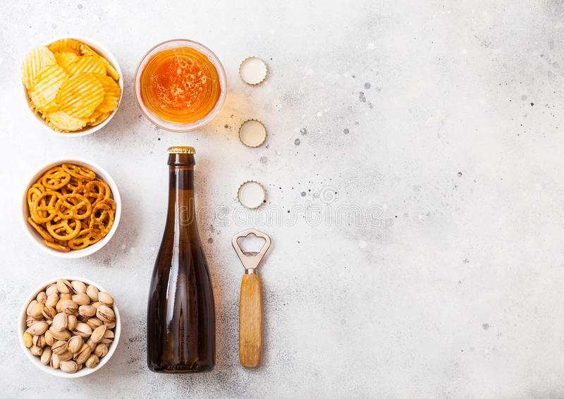 Szkło i butelka rzemiosła lager piwo z przekąską i otwieraczem na kamiennym kuchennego stołu tle Precel wewnątrz, chipsy i pistac zdjęcie stock