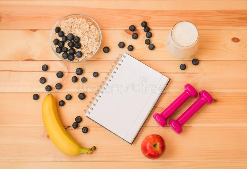 Szkło jogurt, banan, czarne jagody, jabłko, owsa płatek, notatnik i dumbbells na drewnianym tle, obrazy stock