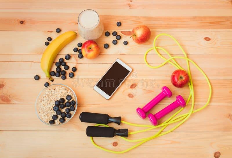 Szkło jogurt, owoc, owsów płatki, skokowa arkana, dumbbells i smartphone na drewnianym tle, fotografia royalty free