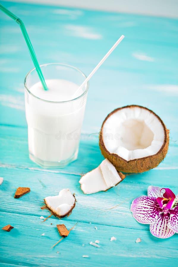 Szkło kokosowy mleko na błękitnym drewnianym stole Dekorujący z Cocon obraz royalty free