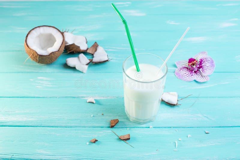 Szkło kokosowy mleko na błękitnym drewnianym stole Dekorujący z Cocon zdjęcia royalty free